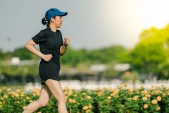 Asian middle-aged woman wearing a black dress, blue hat, running in the park Get the sun light in the morning.  stock photos