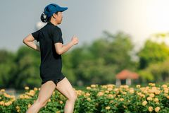 Asian middle-aged woman wearing a black dress, blue hat, running stretching in park near to lake. Get the sun light in the morning.  stock photos