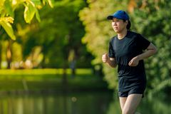 Asian middle-aged woman wearing a black dress, blue hat, running stretching in park near to lake. Get the sun light in the morning.  stock photography