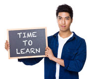 Asian mixed Indian man with blackboard showing the phrases of ti. Me to learn isolated on white Stock Image