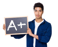Asian mixed Indian man with blackboard showing sign of A plus Stock Photography