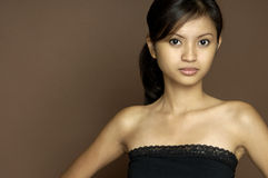 Asian Model 2. A beautiful young asian woman in a black top against a brown background Stock Images
