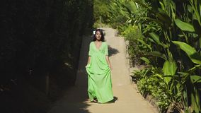 An asian model in a green dress goes on the road in the tropical gaden. Asian young model in a green dress walking on the road among the green tropical plants stock video