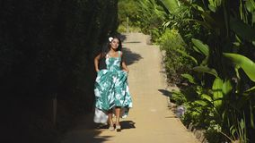 An asian model in a green dress goes on the road in the tropical gaden. An asian young model in a green dress walking on the road among the green tropical stock video footage