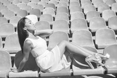 Model posing at the stadium sitting on bright seat Stock Photos
