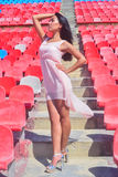 Asian  model posing at the stadium standing in high hills  on brigh Royalty Free Stock Photo