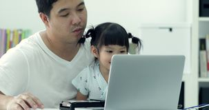 Asian modern family and little girl ,while dad works with notebook stock video