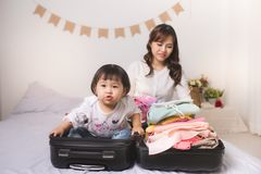Asian mom and baby girl with suitcase baggage and clothes ready. For traveling on vacation Royalty Free Stock Photos