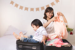 Asian mom and baby girl with suitcase baggage and clothes ready Royalty Free Stock Image