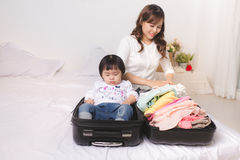 Asian mom and baby girl with suitcase baggage and clothes ready Stock Photography