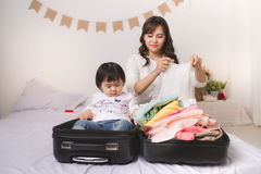 Asian mom and baby girl with suitcase baggage and clothes ready. For traveling on vacation Stock Photo