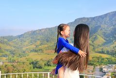 Asian mom cuddle her daughter with love on balcony at hillside.  royalty free stock images