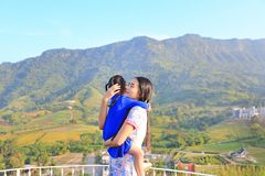Asian mom cuddle her daughter with love on balcony at hillside.  stock photography