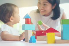 Asian mom and girl kid playing with blocks. Selective focus and Royalty Free Stock Images
