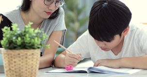 Asian Mom is helping her son to do homework. Of the school at home stock footage