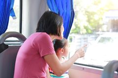 Asian mom and her daughter sitting on public transport bus. Mom pointing something to child girl looking royalty free stock photo