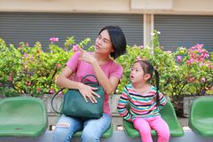 Asian mom and her daughter sitting on public transport bus. Mom pointing something to child girl looking stock images