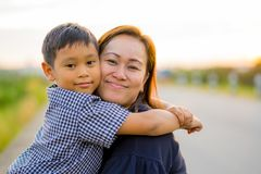 Asian mom hug her young son lovingly at sunset with nature background stock images