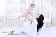 Asian mom lifting a baby Royalty Free Stock Photos