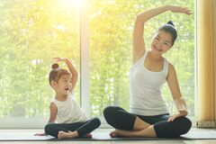 Free Asian Mom Practice Yoga At Home With A Adorable Daughter Sitting Next To Her, Trying To Imitate The Mother`s Posture Stock Image - 191880381