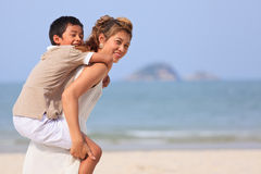 Asian mom and son playing on beach Stock Photo