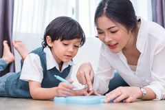 Asian mom teaching cute boy to drawing red heart in board with color pen. Back to school and Education concept. Family and Home. Sweet home theme. Preschool royalty free stock images