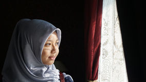 Asian Moslem Looking Out The Window Royalty Free Stock Image