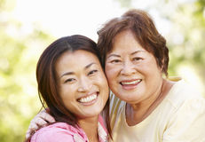 Asian mother and adult daughter head and shoulders outdoors Royalty Free Stock Photography