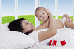 Asian mother with baby in bedroom Stock Images