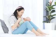 Asian mother and baby son plays at home. Asian mother and baby son plays, hugging, playing at home on bed Stock Photos