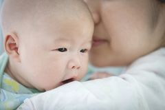 Asian mother and baby son plays at home. Asian mother and baby son plays, hugging, playing at home on bed Royalty Free Stock Images