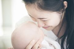 Asian mother and baby son plays at home. Asian mother and baby son plays, hugging, playing at home on bed Stock Photo