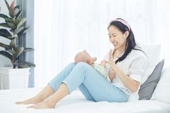 Asian mother and baby son plays at home. Asian mother and baby son plays, hugging, playing at home on bed Royalty Free Stock Photos