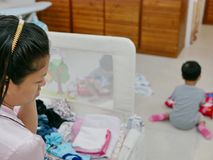 Asian mother being busy folding clothes while taking care of her two daughters at the same time. Selective focus of Asian mother being busy folding clothes while royalty free stock photo