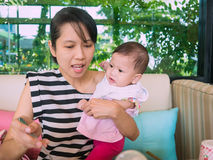 Asian mother carry baby eat meal in house. Royalty Free Stock Image