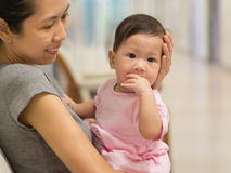 Asian mother carry baby indoor. Stock Images
