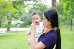 Free Asian Mother Carrying Her Infant Baby Boy In The Summer Garden Stock Image - 130511731