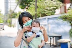 Asian mother carrying her infant baby by hipseat outdoor with wearing a protection mask against PM 2.5 air pollution in Bangkok stock photo