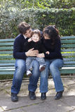Asian mother caucasian father and child on a parkbench Stock Image
