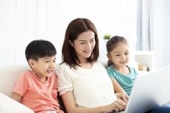 Mother with children in living room with laptop. Asian mother with children in living room with laptop Royalty Free Stock Photo