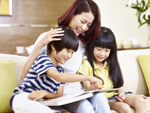 Asian mother and children reading a book together. Young asian mother and children sitting on couch at home reading a book together, happy and smiling royalty free stock images