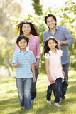 Asian mother and children running hand in hand in park Royalty Free Stock Images