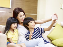 Asian mother and children taking a selfie at home. Young asian mother and children sitting on sofa taking a selfie with mobile phone, happy and smiling stock photography