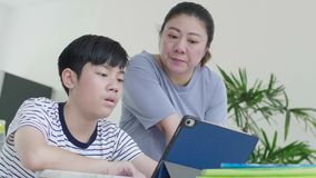 Asian mother is controlling her son to do the homework.