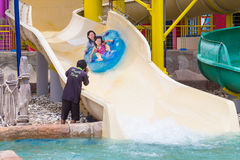 Asian mother and daughter being photograph riding air tube down stock photo