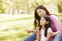 Asian mother and daughter blowing bubbles in park Stock Photos