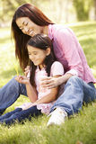 Asian mother and daughter blowing bubbles in park Stock Photo