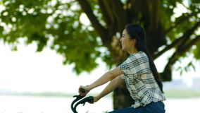 Asian mother & daughter cycling on lakeside promenade in summer. Asian mother & daughter enjoying cycling on lakeside promenade in summer stock video footage