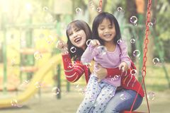 Asian mother and daughter having fun with bubbles. Asian mother and daughter plays with soap bubbles at playground Stock Images
