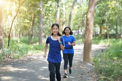 Mother and daughter jogging in a park. royalty free stock photo